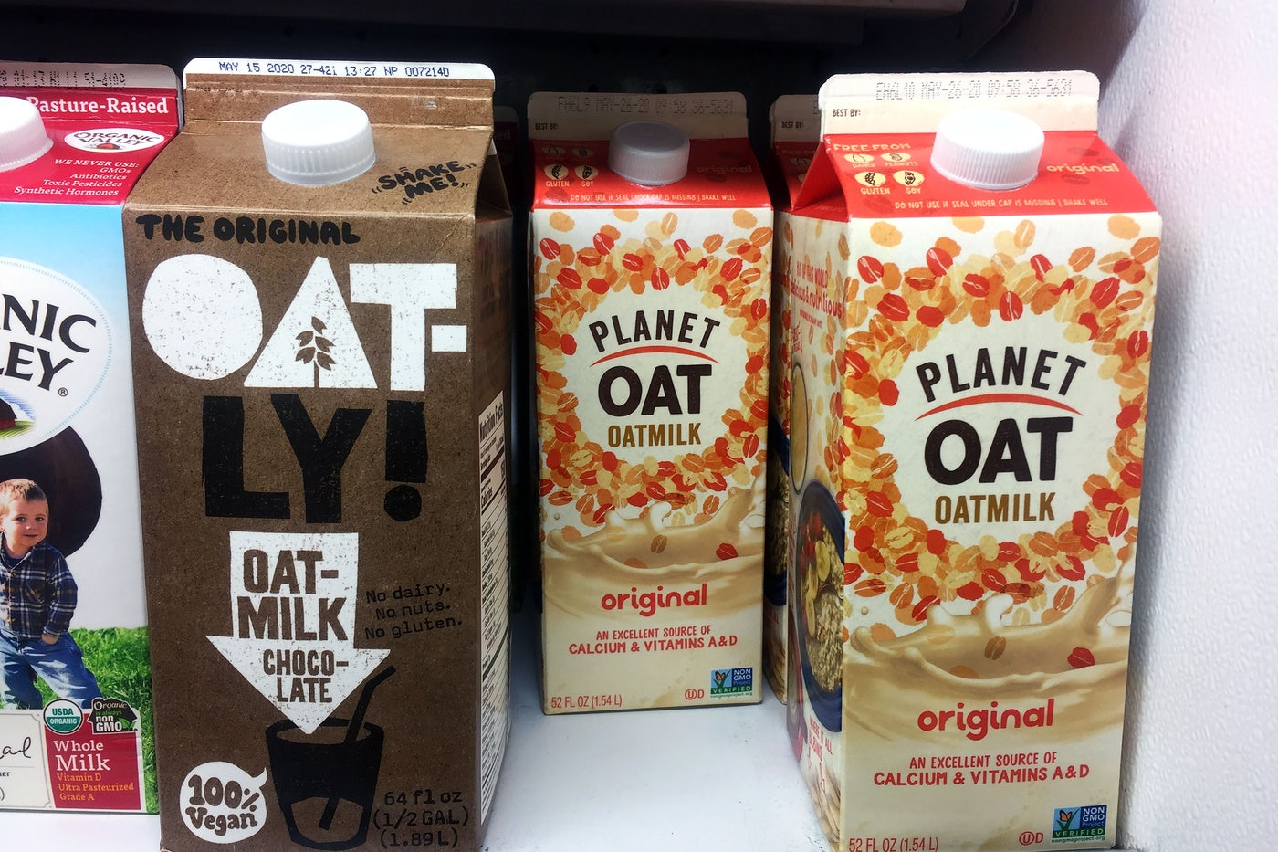 Oatly and Planet Oat oat milk stand on a supermarket shelf.