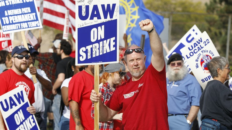A United Auto Workers union member raises his fist on the picket line at the General Motors Flint Assembly plant.