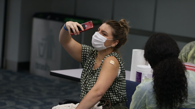 A woman takes a selfie after receiving a Covid shot.
