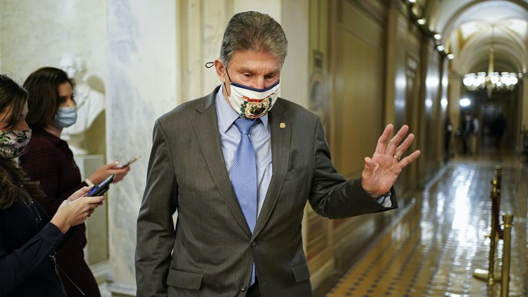 A masked Joe Manchin passes by reporters as he departs Capitol Hill.