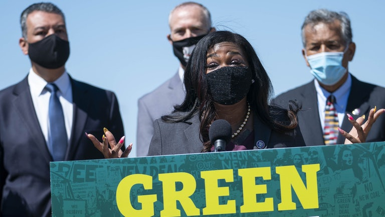 Congresswoman Cori Bush speaks, wearing a face mask, at a podium reading