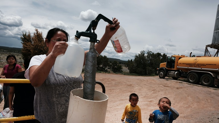 A woman fills water jugs at a public tap.