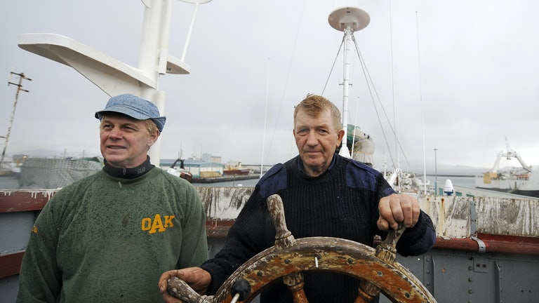 Whaler and captain Olafur Olafsson and his number two Hafstian Omar thorstainsson stand at the helm of a restored whaling vessel.