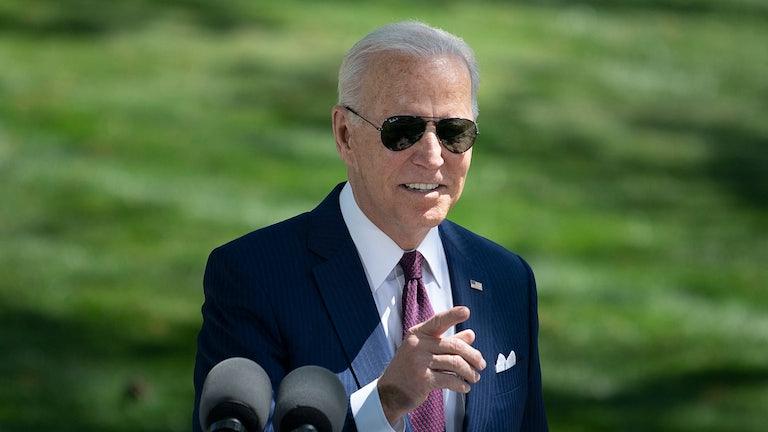 Joe Biden, wearing sunglasses, gestures.