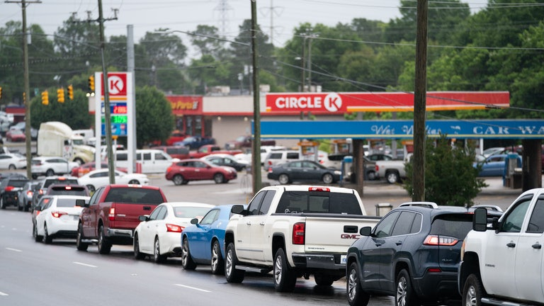 Cars on the road wait in line to drive into a gas station.