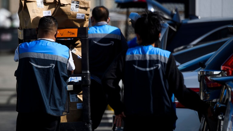 An Amazon delivery driver scans bags of groceries while loading a vehicle outside of a distribution facility