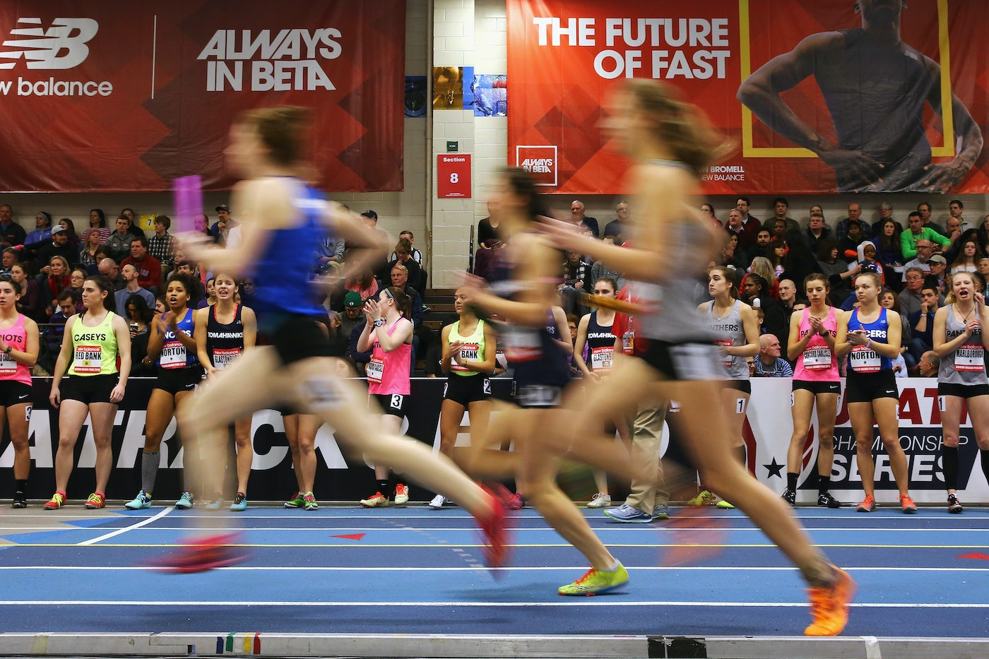Three young women runners run by, blurred, on an indoor track, as other young runners and spectators look on.