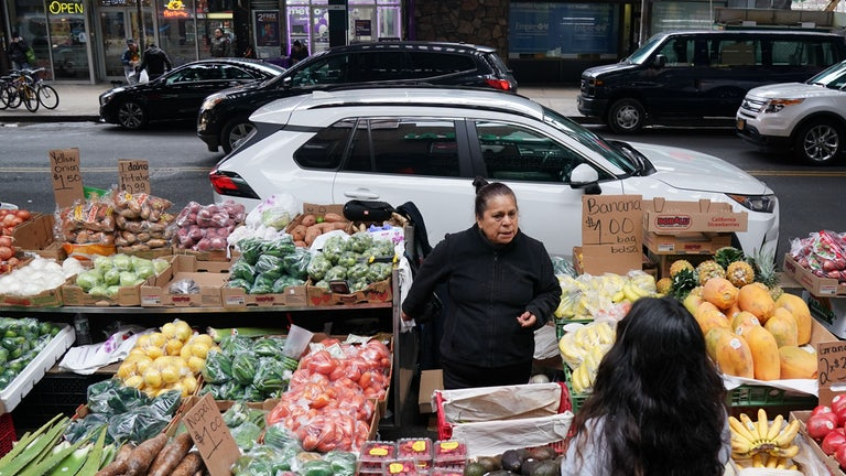 A woman sells produce on a street in the Queens in November of 2019.