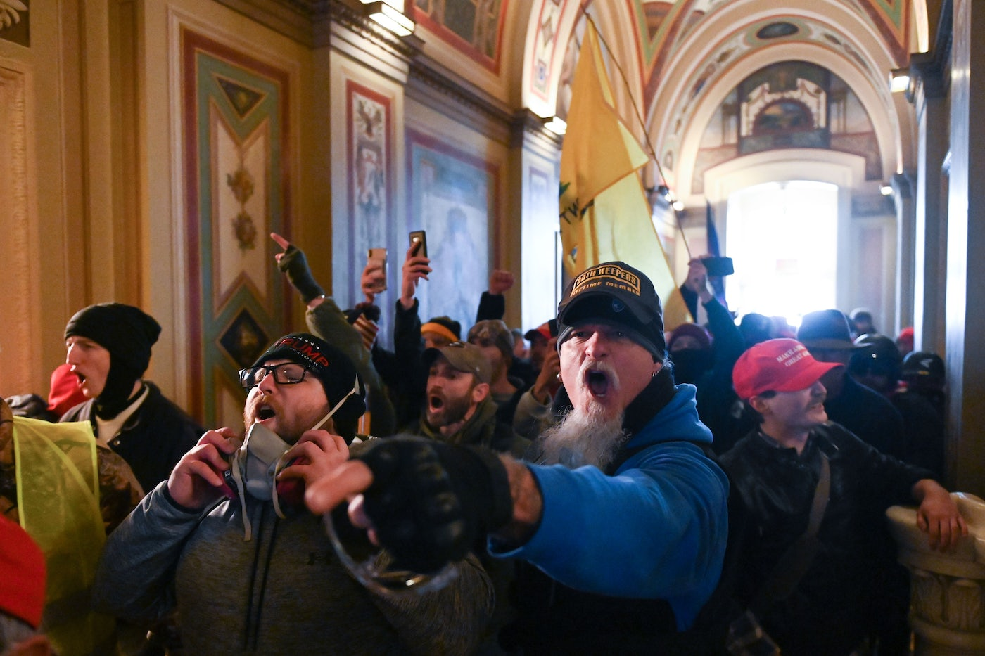 Maskless Trump supporters stand shoulder to shoulder and shout in the U.S. Capitol.