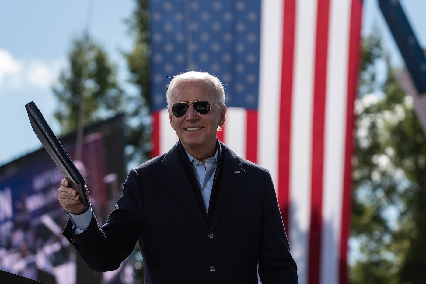 Democratic presidential nominee Joe Biden holds a binder in front of an American flag at a campaign event.
