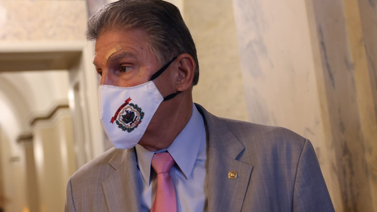 Joe Manchin looks to his right, wearing a face mask.