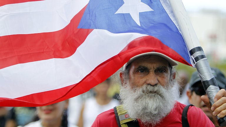 A man carries a Puerto Rican flag during a protest in San Juan