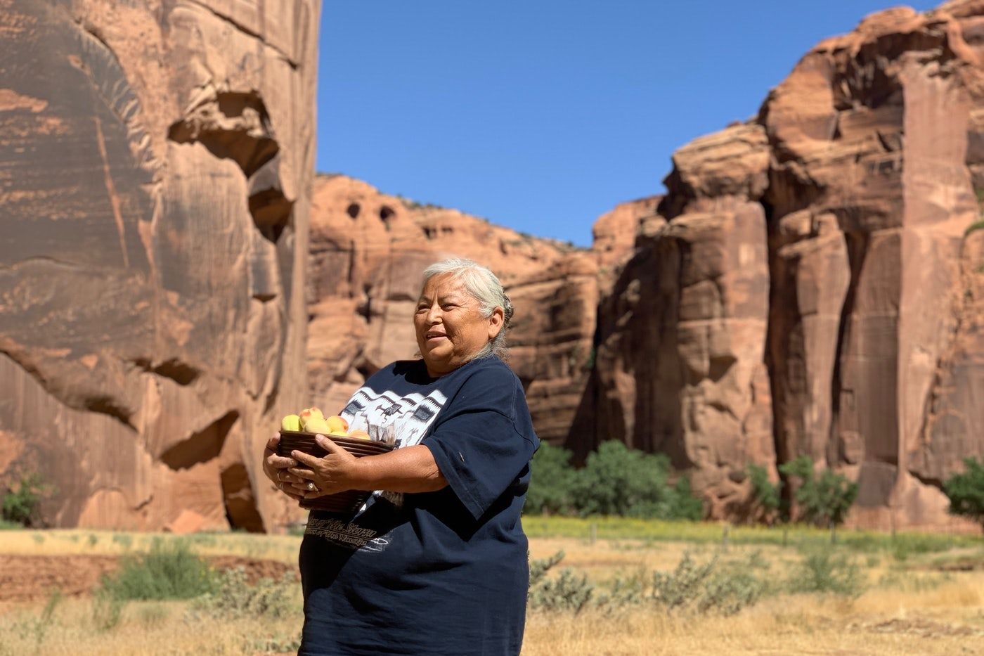 Sylvia Watchman holds a basket of peaches in Canyon de Chelly.