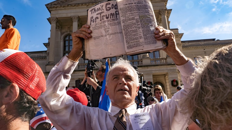 A preacher holds up his Bible while supporters of Donald Trump host a 'Stop the Steal' protest outside of the Georgia State Capital building.