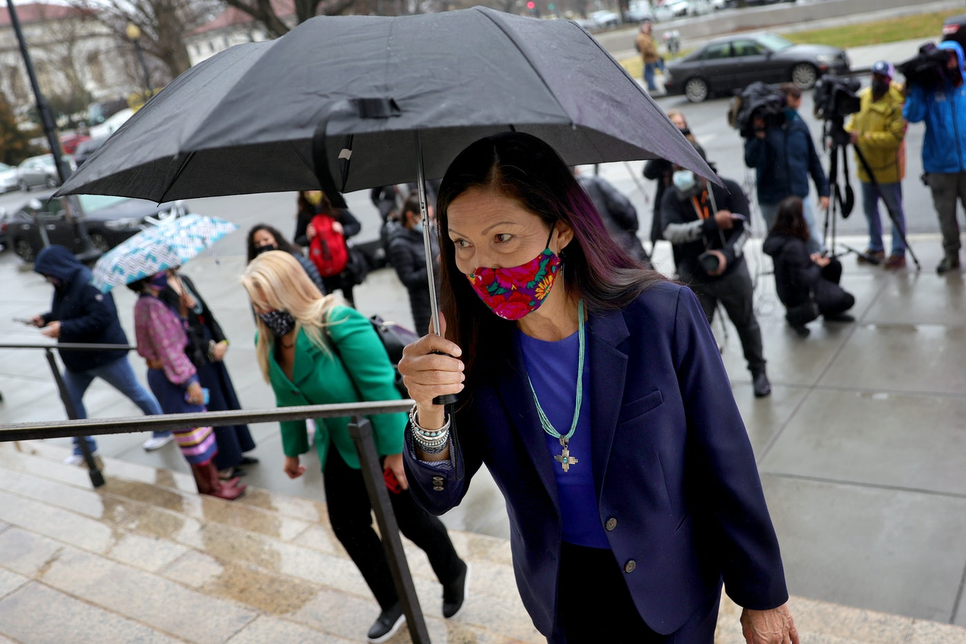 Deb Haaland walks up steps holding an umbrella.