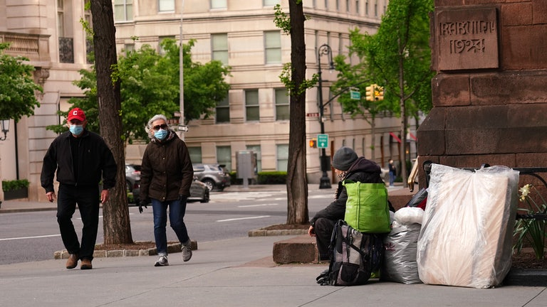An unhoused person sitting on the sidewalk in Manhattan as pedestrians pass.