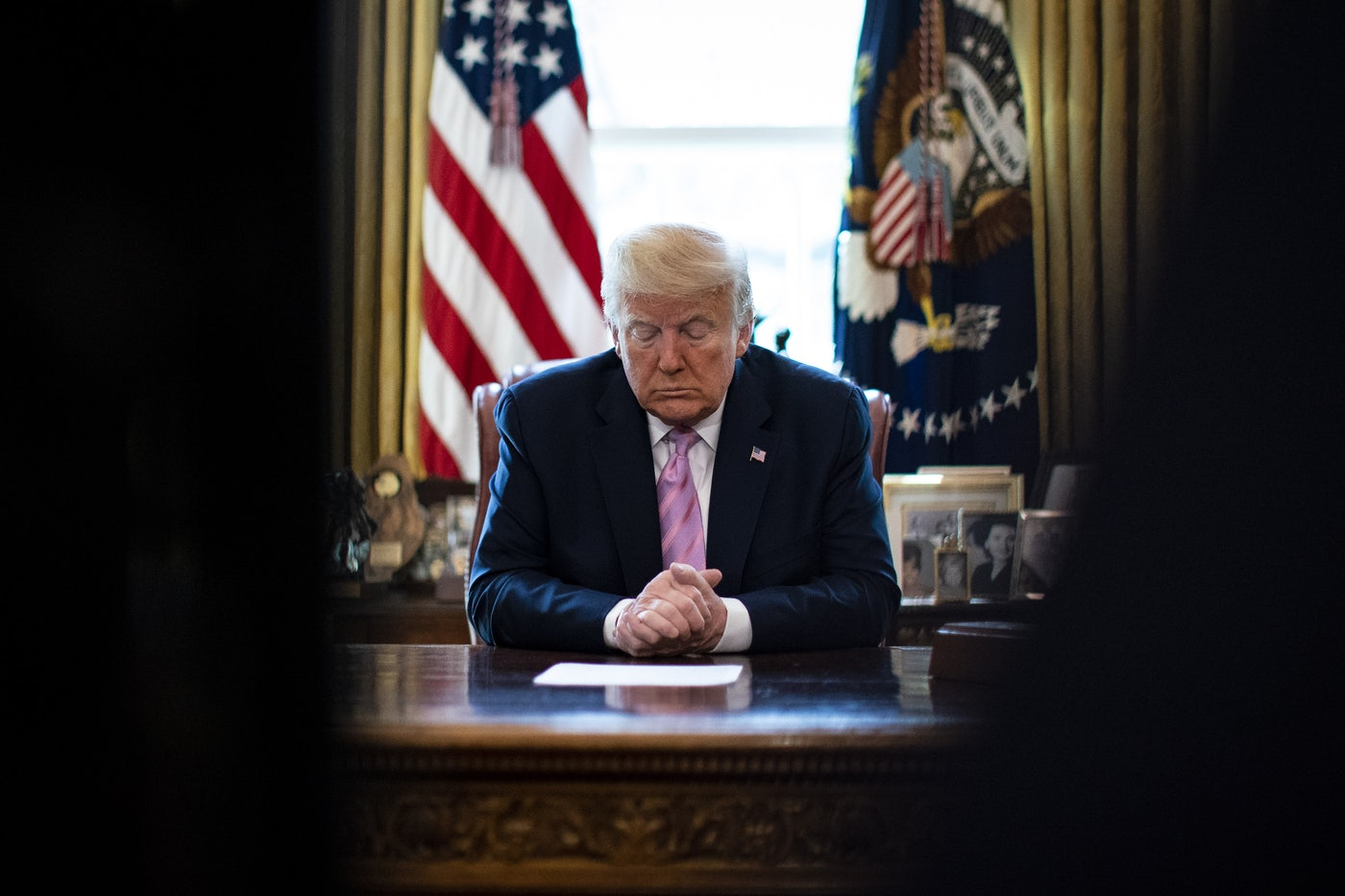 President Donald Trump bows his head in the Oval Office of the White House