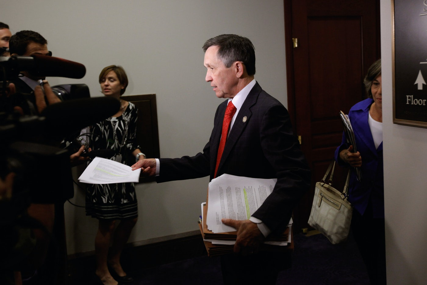 Dennis Kucinich hands out copies of a CBO report to reporters