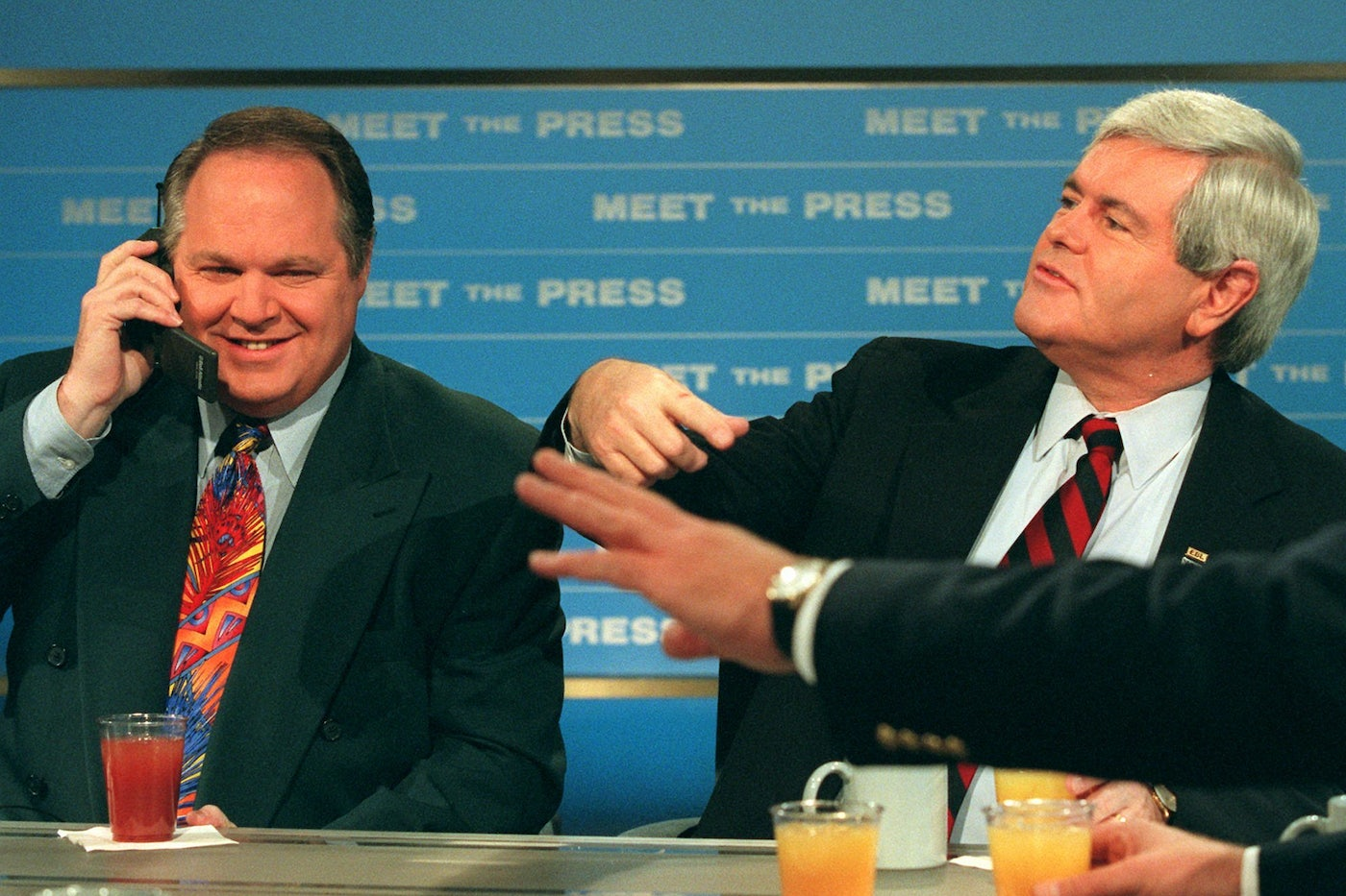 "Radio talk show host Rush Limbaugh talks on a phone as House Speaker Newt Gingrich gestures during a break in taping of NBC's ""Meet the Press"""