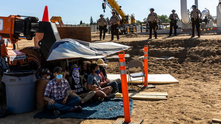 Activists sit beneath a tarp as law enforcement officers line up in front of construction equipment.