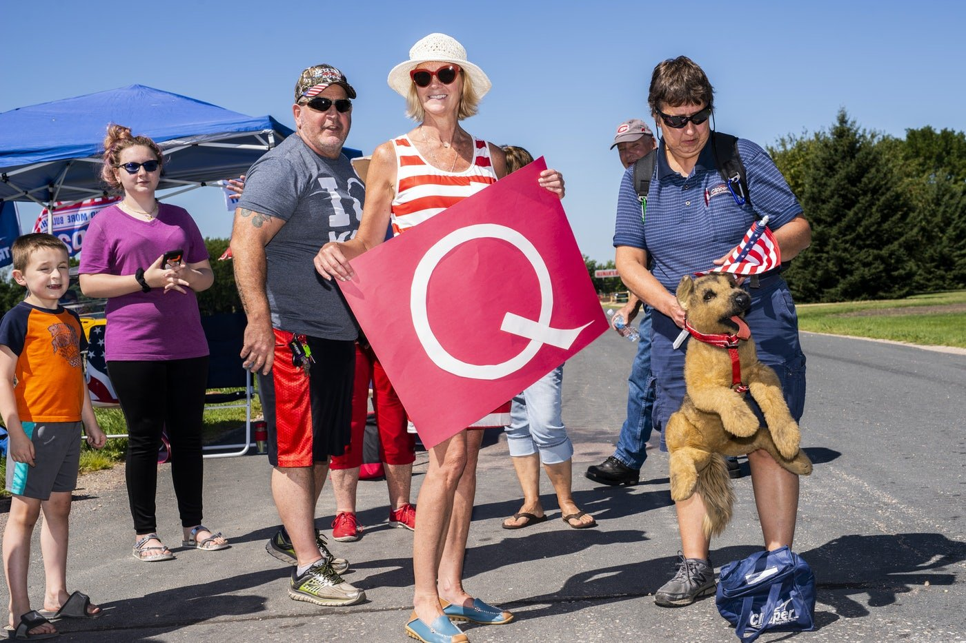 """QAnon supporters hold a """"Q"""" banner at a Trump campaign stop this summer."""