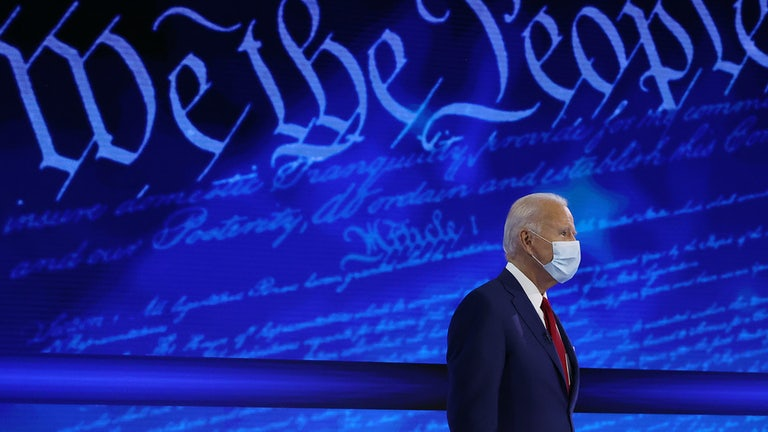 "Joe Biden stands in front of a background reading ""We the People."""
