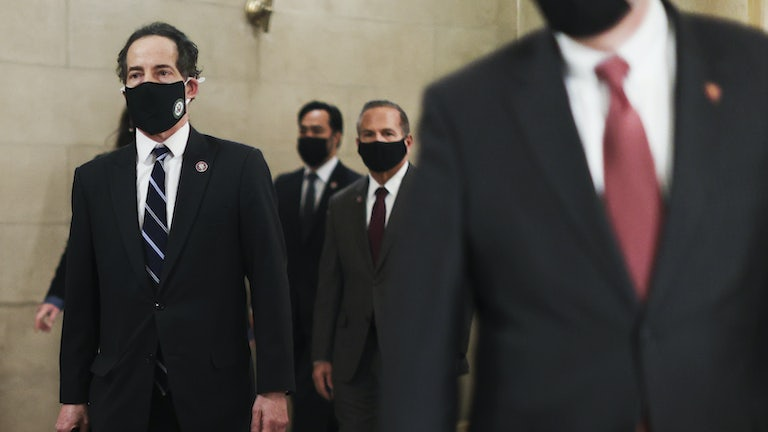 Representative Jamie Raskin of Maryland, in a mask, walks through the Capitol with the articles of impeachment.