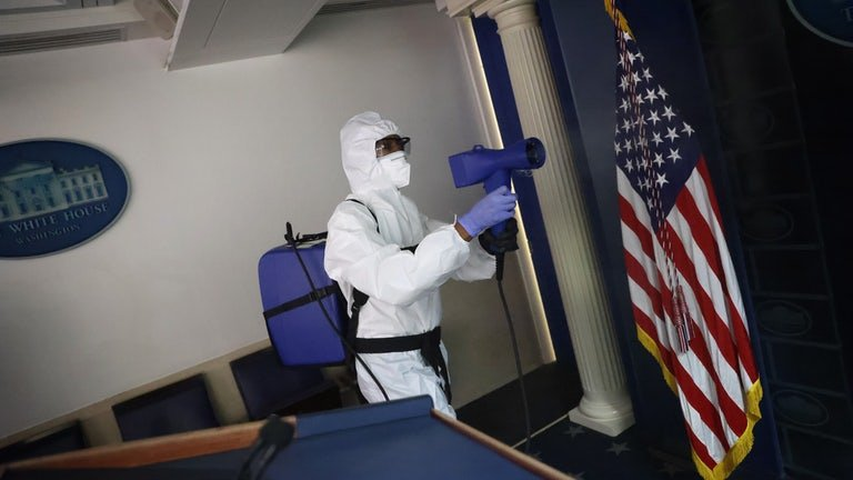 A member of the White House cleaning staff sanitizes the James S. Brady Press Briefing Room as a precaution after President Donald Trump, several members of his staff, and three members of the press corps tested positive for coronavirus.