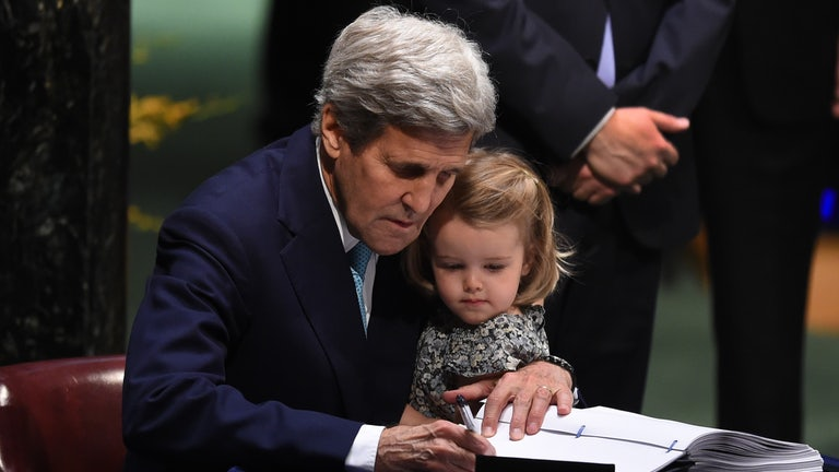 John Kerry holds his granddaughter while signing a Paris Agreement document.