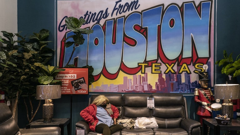 "A masked woman sits on a couch at a furniture store turned warming station in front of a large sign reading ""Greetings from Houston Texas"""