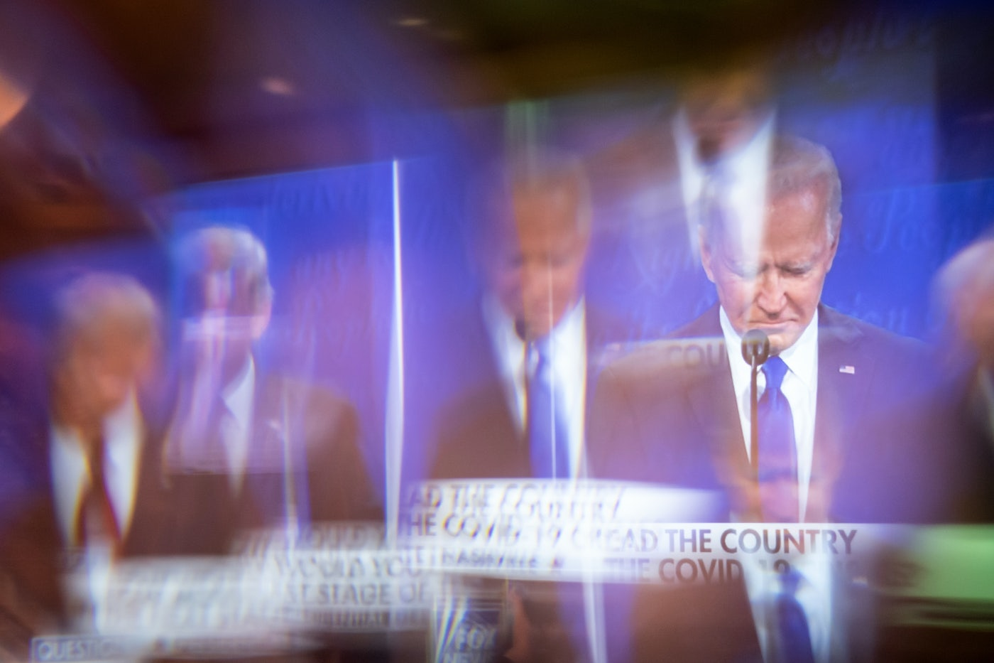 Former Vice President Joe Biden is seen on-screen through a window at a presidential debate watch party.