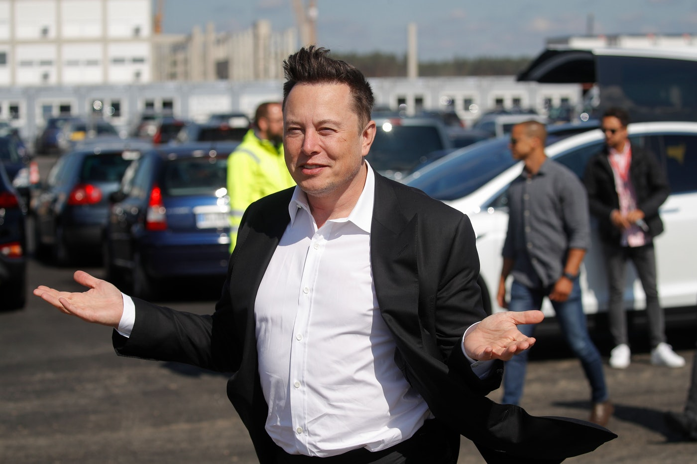 Elon Musk, standing before a fleet of cars, with hair and jacket swept up by the breeze