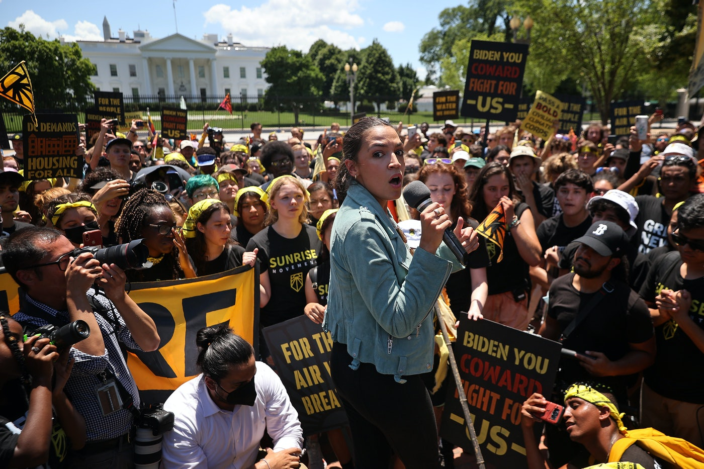 Alexandria Ocasio-Cortez holds a microphone, surrounded by activists.