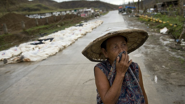 A woman walks past the bodies of Typhoon Haiyan victims awaiting burial in a mass grave in the Philippines.