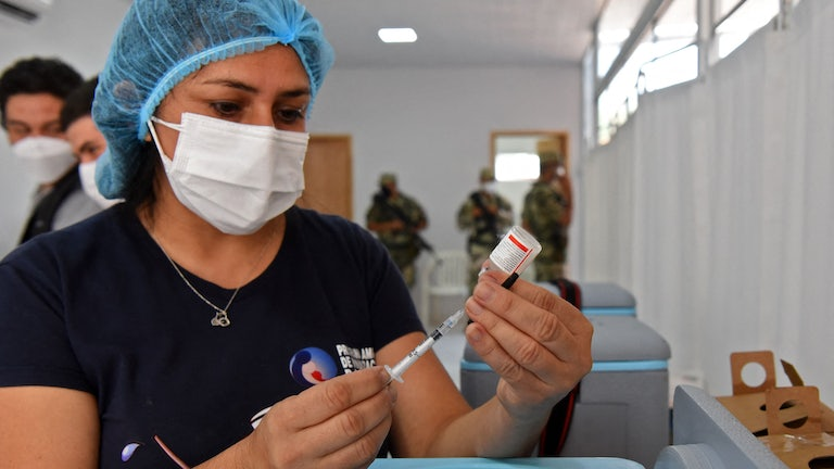 A nurse fills a syringe from a vial.