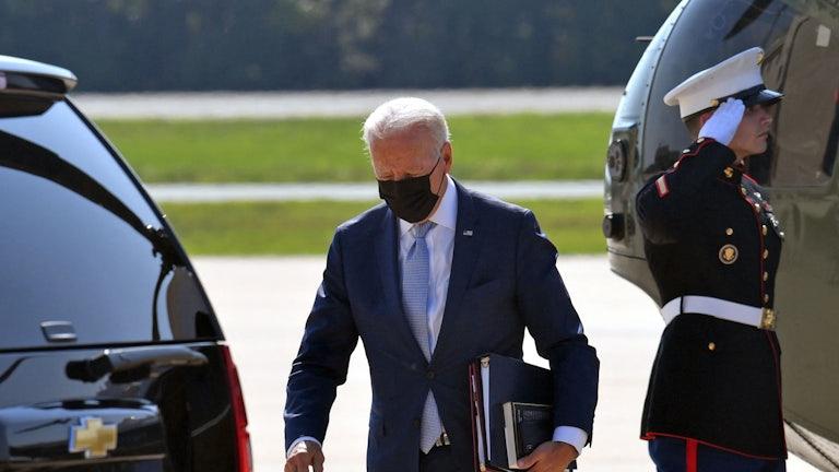 President Biden carries folders away from Marine One.