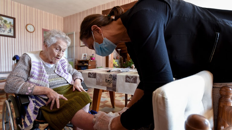 A nurse examines a woman's leg.