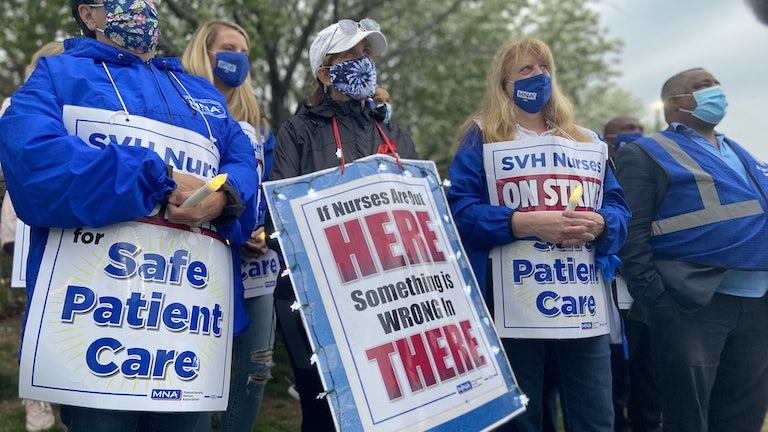 Nurses wear protest signs and hold candles during a strike vigil at Saint Vincent Hospital in Worcester, Massachusetts.