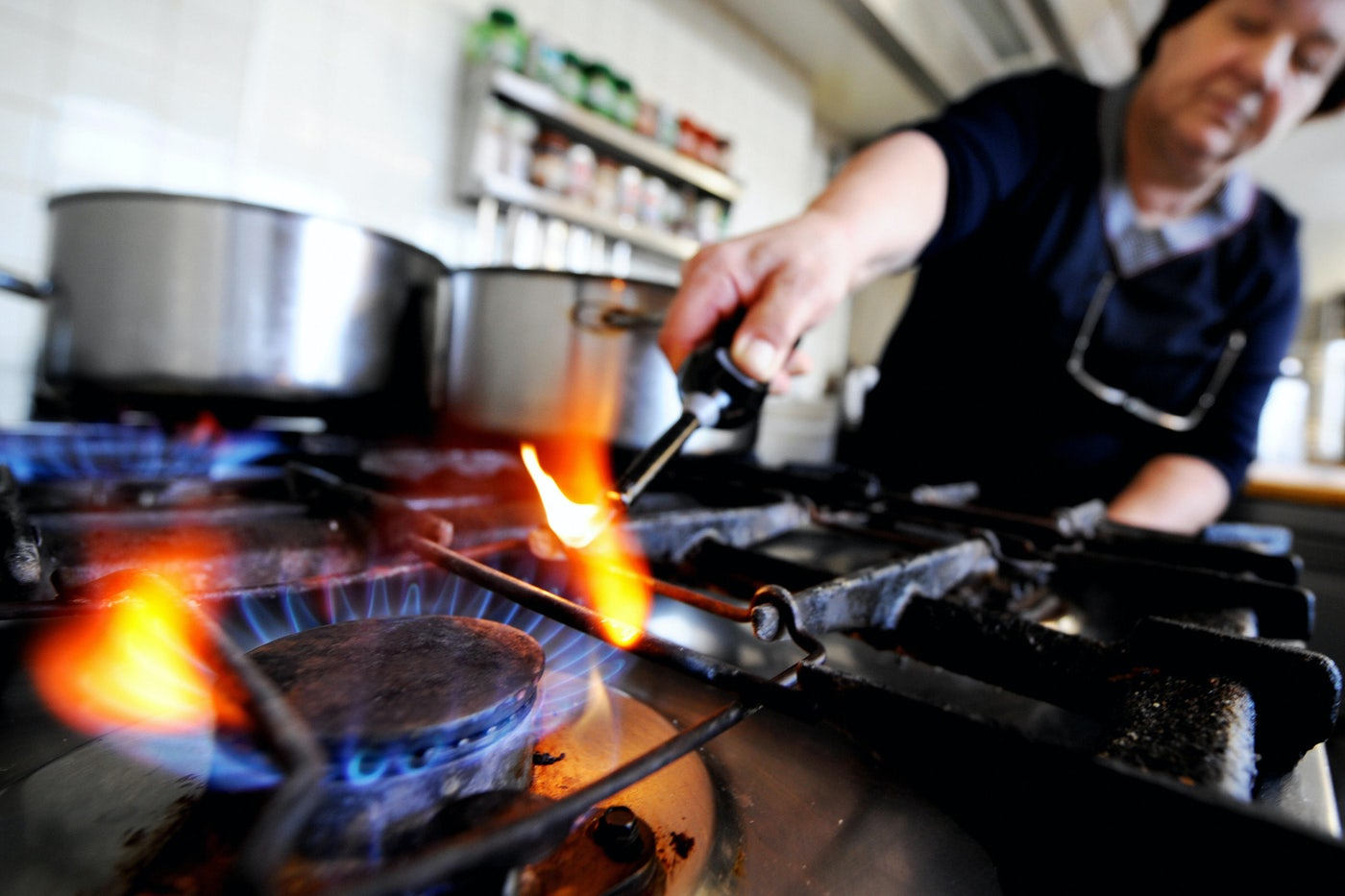 A person lights a gas stove.