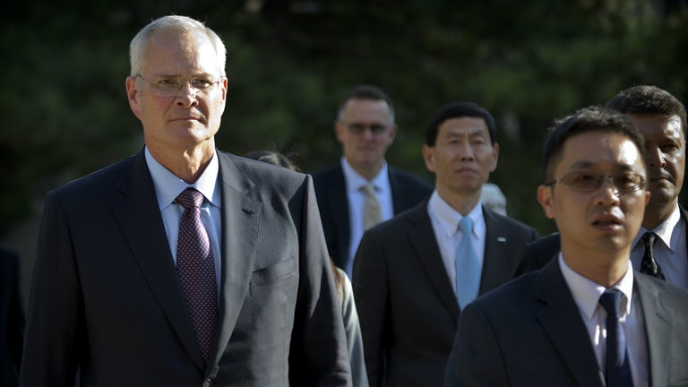 Exxon Mobil CEO Darren Woods walks with several other people.