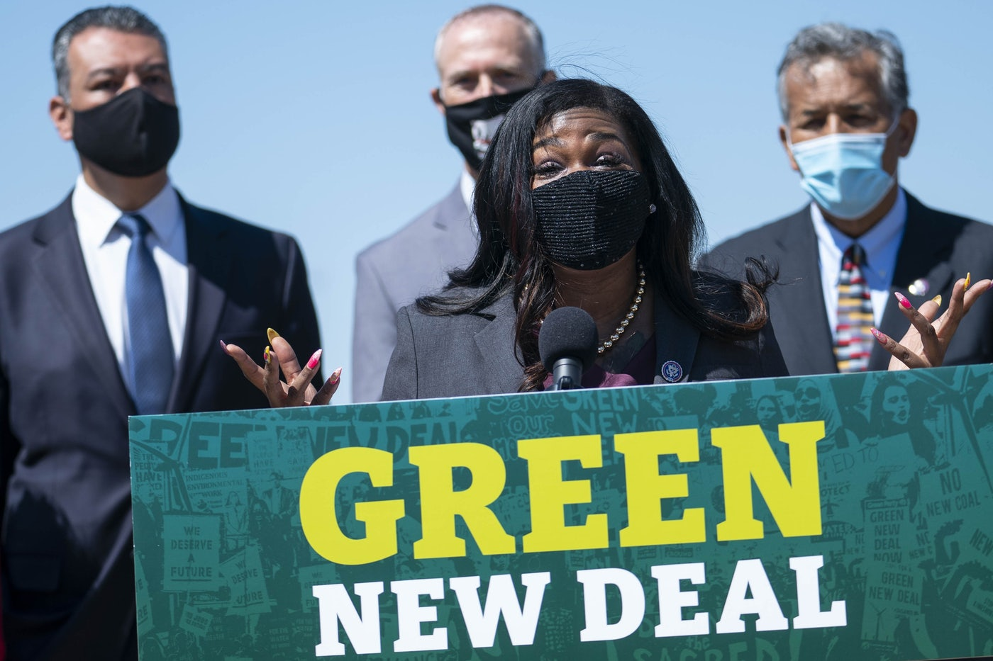 "Congresswoman Cori Bush speaks, wearing a face mask, at a podium reading ""Green New Deal."""