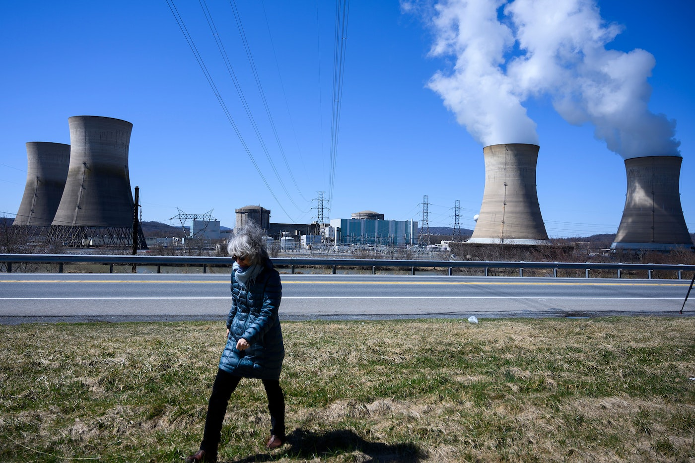 A woman walks past the nuclear plant on Three Mile Island.