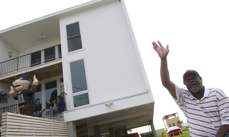 Lower Ninth Ward resident Robert Green Sr., waves to passing cars outside his new home in 2010. (Getty Images/AFP/Rod Lamkey JR)
