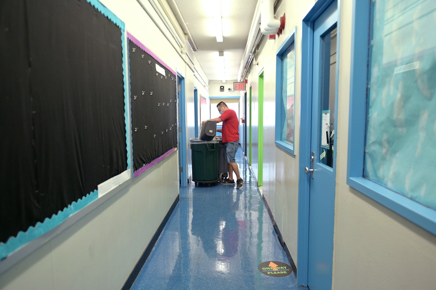 A worker at a public school in New York City cleans a hallway.