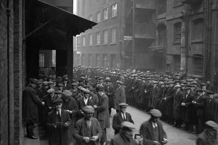 A large quantity of men stand assembled in a dockyard.