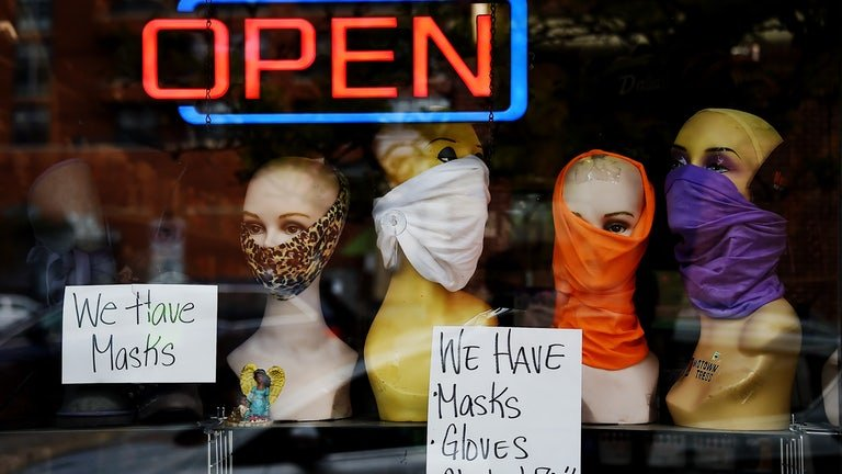 Mannequin heads wear masks in the window of a small boutique