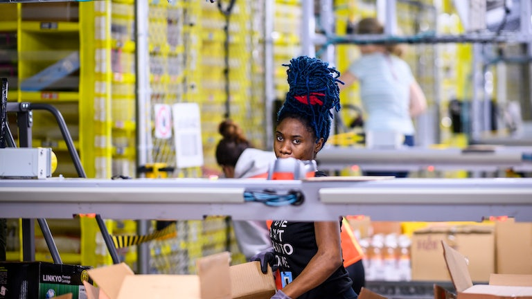 An Amazon warehouse worker loads boxes at a fulfillment center in Staten Island.