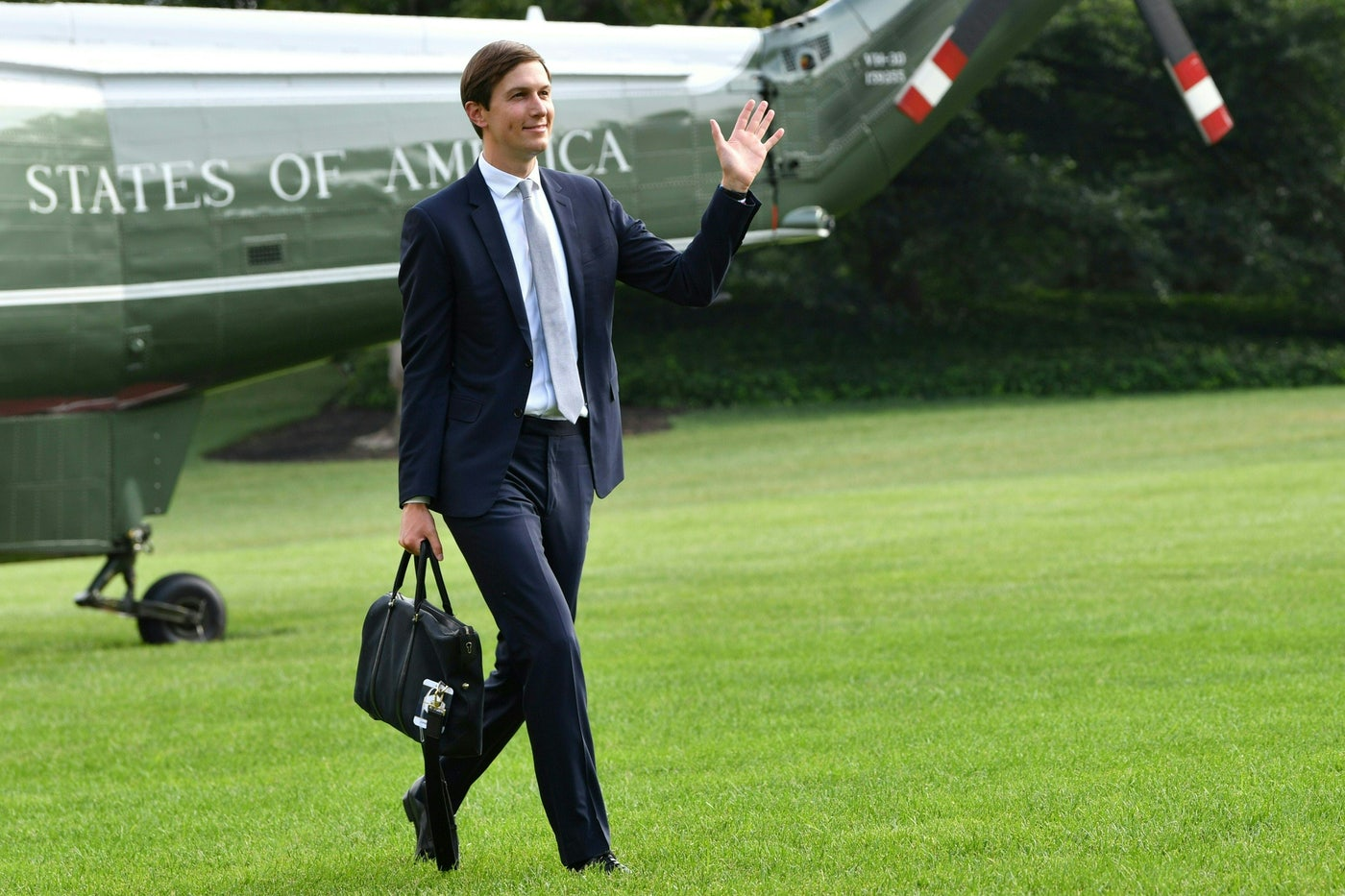 Jared Kushner waves as he returns to the White House