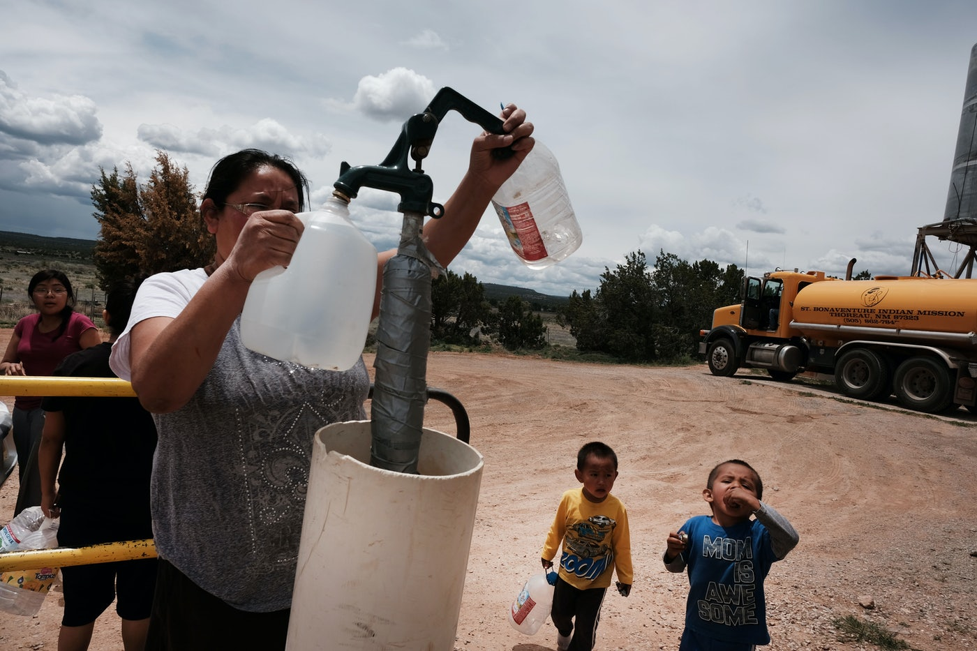 A woman fills water jugs at a public tap.