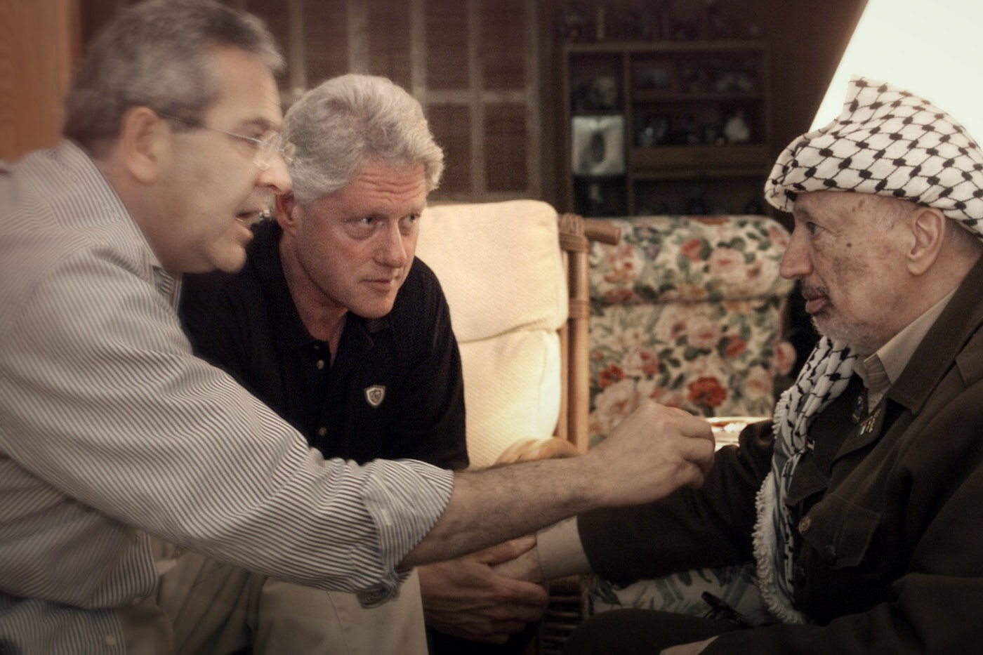 President Bill Clinton and Gamal Hamal speak closely with Yasser Arafat, touching his arm.